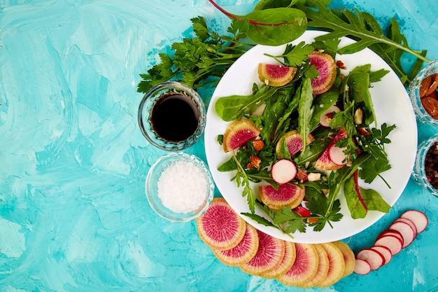 Salade dans une assiette blanche autour d'ingrédient