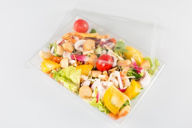 Salade dans une boîte à emporter en plastique isolé sur blanc