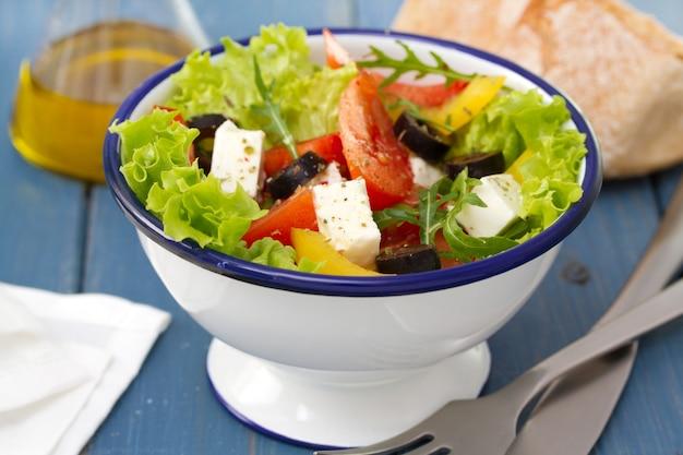 Salade dans un bol avec du pain et de l'huile