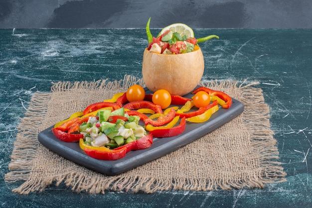 Salade dans une citrouille sculptée avec des ingrédients mélangés.