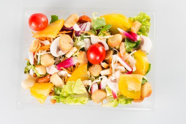 Salade dans un récipient à emporter sur fond blanc en vue de dessus