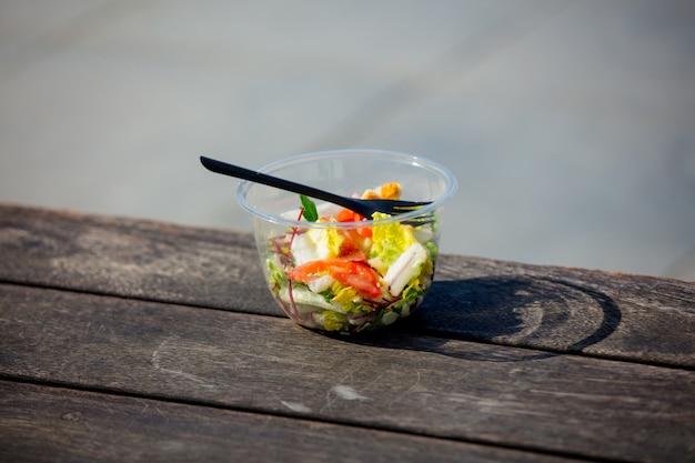 Salade déjeuner avec une fourchette dans une boîte en plastique sur un banch en bois