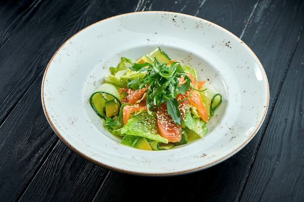 Salade diététique appétissante avec laitue, concombre, avocat et saumon légèrement salé dans une assiette blanche sur fond de bois sombre. la nourriture saine
