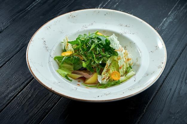 Salade diététique appétissante avec roquette, sauce, laitue et boeuf chaud dans une assiette blanche sur fond de bois sombre.