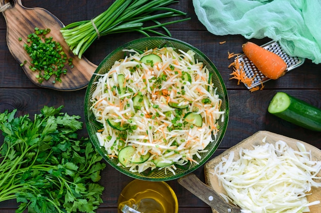 Salade diététique au chou, concombre, carotte, légumes verts. salade de printemps juteuse avec des légumes frais sur une table en bois. nutrition adéquat. vue de dessus.