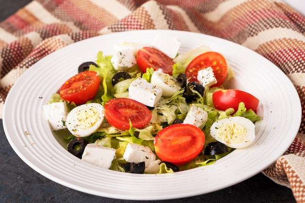 Salade diététique aux légumes frais. tomates, œufs de caille, laitue, fromage et olives noires.
