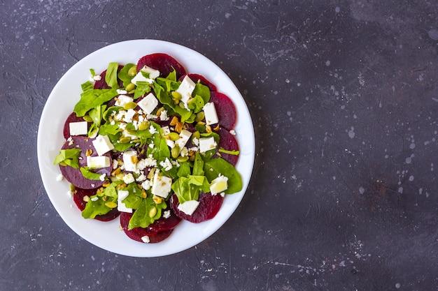 Salade diététique de betterave, de roquette, de fromage feta, de graines de citrouille à l'huile d'olive sur fond noir.
