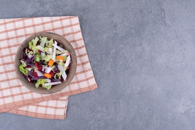 Salade diététique dans une assiette en bois avec des ingrédients mélangés