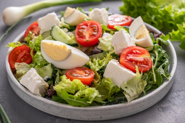 Salade diététique avec des légumes verts frais, des œufs, des tomates et du fromage gros plan