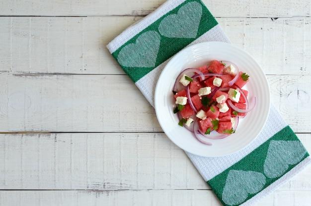 Salade diététique de pastèque fraîche, oignon bleu et fromage de chèvre (feta). vue de dessus