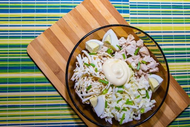 Salade diététique pour une bonne nutrition avec du poulet et des œufs sur un tapis vert.