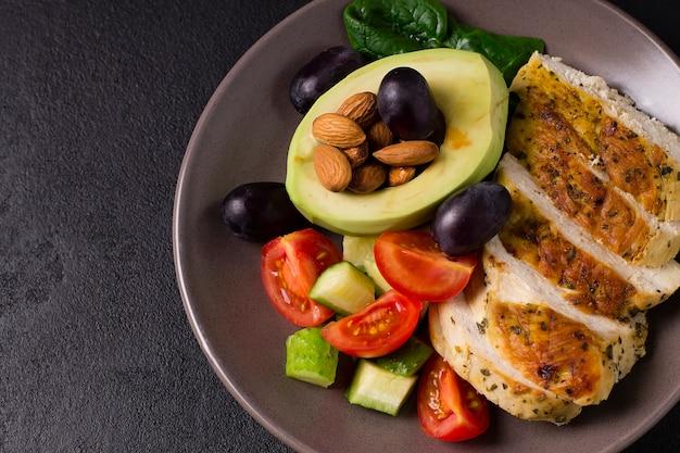 Salade diététique saine avec filet de poulet, avocat, noix et légumes frais.