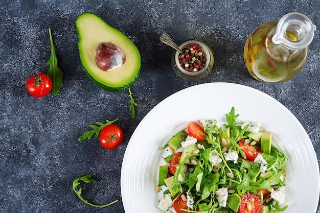 Salade diététique avec tomates, fromage bleu, avocat, roquette et pignons de pin. vue de dessus. lay plat.