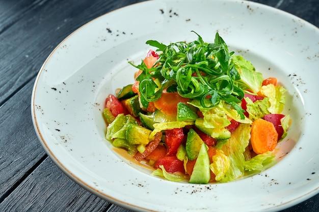 Salade diététique et végétarienne de légumes mélangés et de laitue avec sauce aux arachides, servie dans une assiette blanche sur une table en bois noir