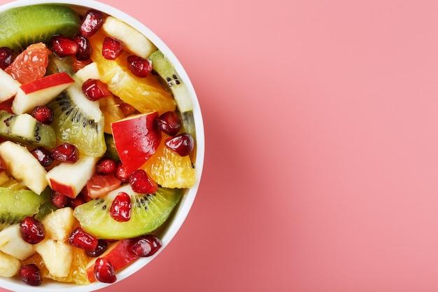 Salade de différents fruits mûrs juteux dans une tasse blanche sur fond rose. espace libre
