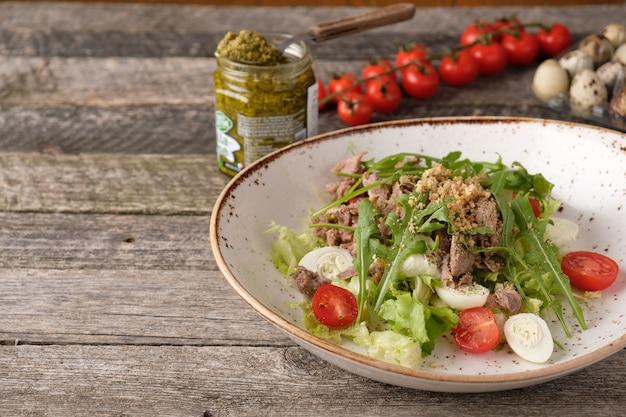 Salade de dinde aux œufs de caille, tomates et noix sur une assiette copy space