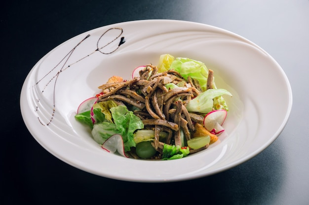 Salade du chef avec radis de boeuf frais avec légumes et vinaigrette au vinaigre balsamique évaporé