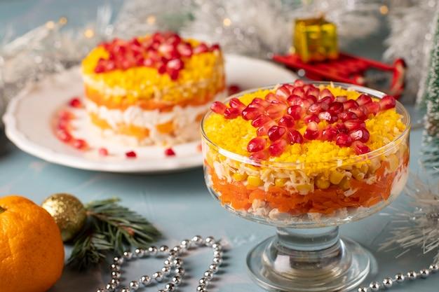 Salade du nouvel an au poulet, œufs et maïs, décorée d'une étoile de graines de grenade