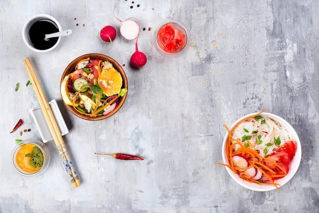 Salade épicée asiatique de nouilles de verre ou de funchoza avec salade de carottes et de légumes sur fond de pierre