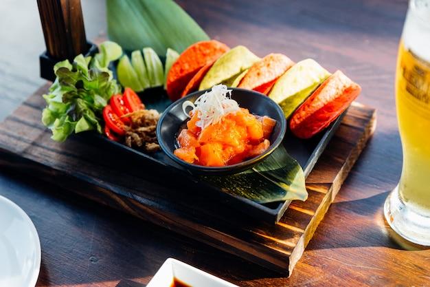 Salade épicée au saumon cru servie avec des croustilles croustillantes rouges et vertes pour le canape et la bière froide.