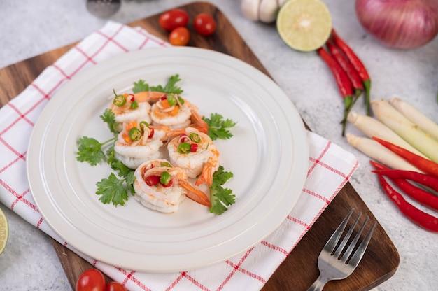Salade épicée aux crevettes sur une plaque blanche. nourriture thaï.