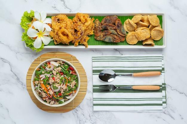 Salade épicée mixte avec saucisse vietnamienne, œuf en conserve et calamars croustillants, cuisine thaïlandaise.