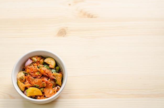 Salade épicée de moules marinées sur une table en bois, cuisine thaïlandaise.