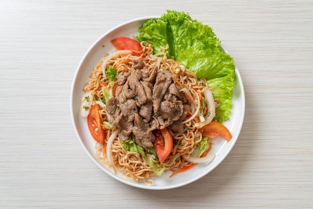 Salade épicée de nouilles instantanées au porc sur plaque blanche