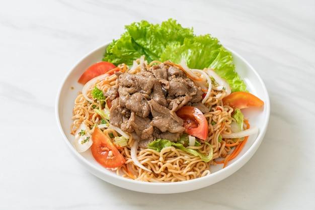 Salade épicée de nouilles instantanées avec du porc sur une assiette blanche - style cuisine asiatique