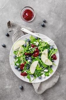 Salade estivale avec feuilles de salade, fruits, baies et fromage