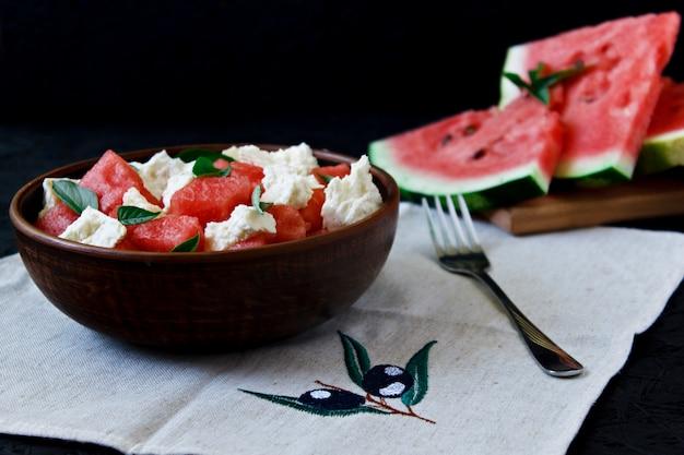 Salade d'été au melon d'eau, fromage blanc et basilic dans une assiette en argile sur fond noir