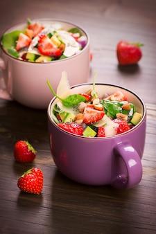Salade d'été aux fraises, avocat et épinards sur fond en bois rustique