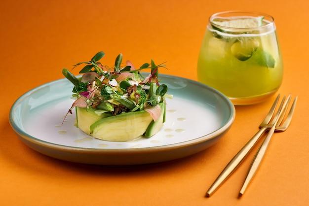 Salade d'été fraîche d'avocat, brocoli et jeunes haricots fond orange