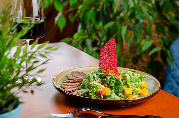 Salade exotique avec magret de canard, mangue, roquette fraîche et laitue servie avec vin rouge sur table en bois.