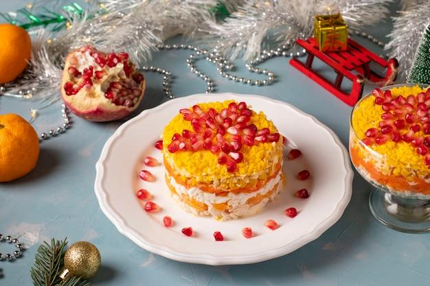 Salade festive du nouvel an au poulet, œufs, carottes et maïs, décorée d'une étoile de graines de grenade sur fond bleu clair