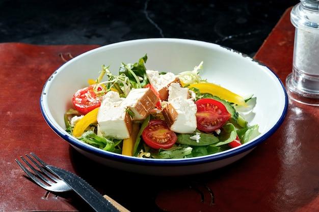 Salade de feta fumée, tomates cerises, poivrons et épinards dans une assiette blanche. surface sombre. lumière forte