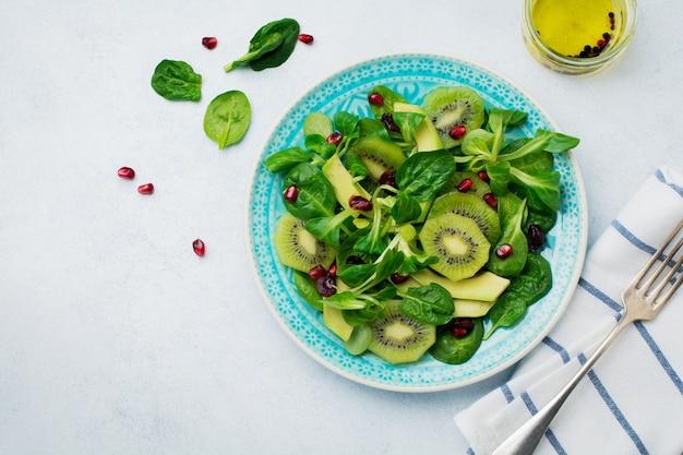 Salade de feuilles de bébé épinards, cresson, kiwi, avocat et grenade dans une plaque en céramique bleue sur une surface en bois clair blanche. mise au point sélective. vue de dessus. copiez l'espace.