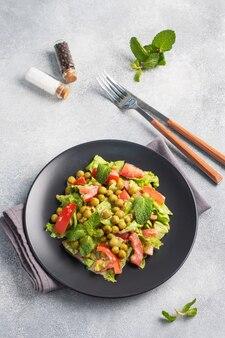Salade de feuilles de tomates vertes et de pois en conserve assaisonnés de sauce sur une assiette noire. salade diététique fraîche de printemps. vue de dessus