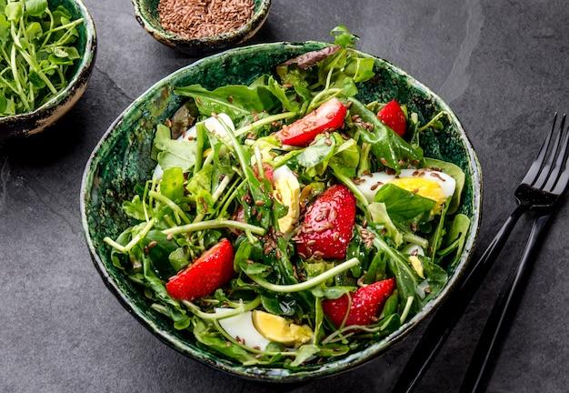 Salade de feuilles vertes et de fraise avec des graines de lin dans un bol vert