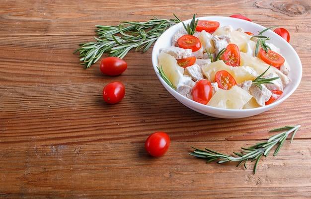 Salade de filet de poulet au romarin, ananas et tomates cerises sur bois brun