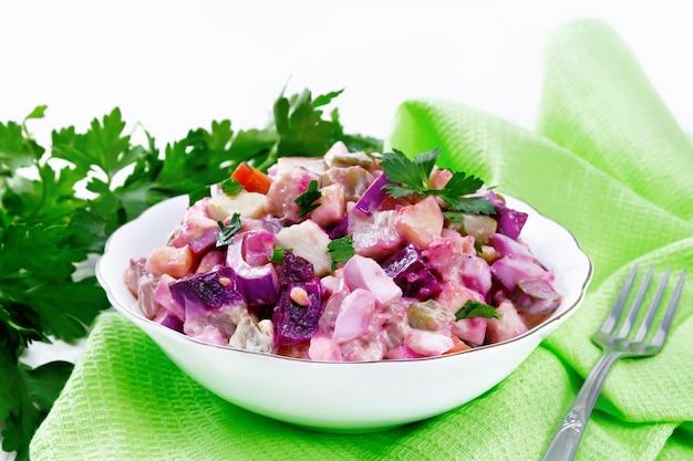 Salade finlandaise rosoli de hareng, betteraves, pommes de terre, concombres marinés ou marinés, carottes, oignons et œufs, habillés de mayonnaise dans un bol sur fond de planche de bois