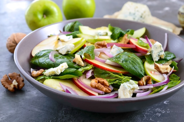 Salade de fitness diététique savoureuse avec épinards, pommes, oignons rouges, fromage bleu, noix