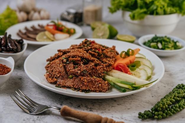 Salade de foie de porc avec chili, riz rôti, oignon nouveau, carotte et concombre.