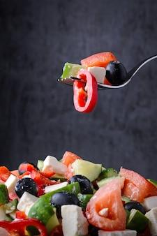 Salade sur une fourchette sur une assiette sur un fond sombre