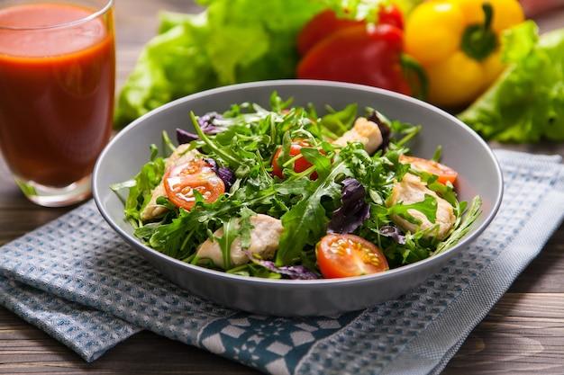 Salade fraîche au poulet, tomates, roquette, mesclun, basilic et jus de tomates sur une serviette en tissu, sur une table en bois