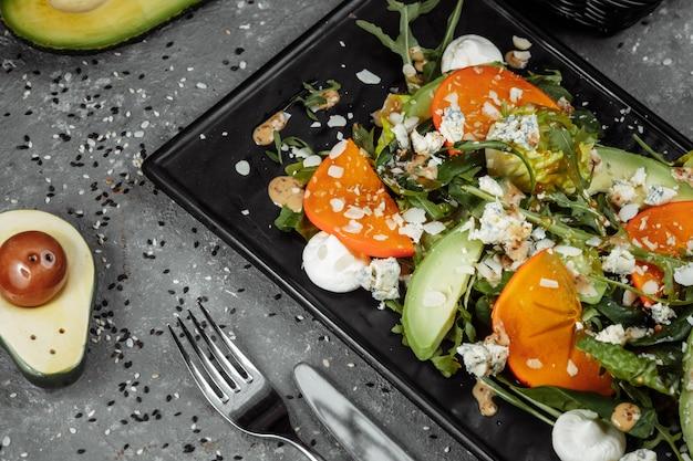 Salade fraîche aux fruits et légumes verts sur fond de toile sombre. nourriture saine.