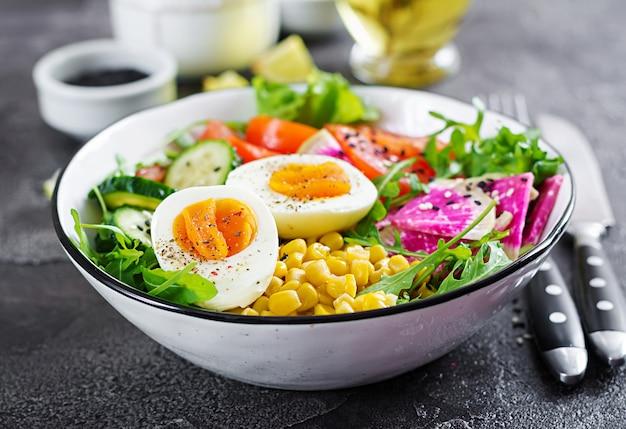 Salade fraiche. bol de légumes crus frais - concombre, tomate, radis pastèque, laitue, roquette, maïs et œuf à la coque. nourriture saine. bol de bouddha végétarien.