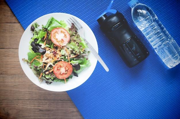 Salade fraîche et bouteille d'eau sur tapis de yoga, mode de vie sain et concept d'entraînement