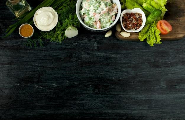 Salade fraîche dans une assiette sur une surface sombre.