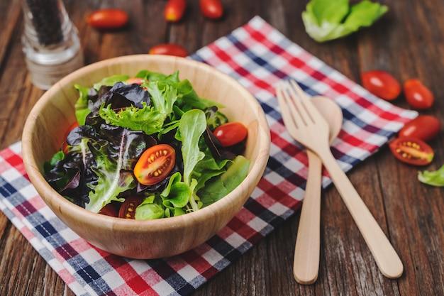 Salade fraîche dans un bol en bois sur une table en bois rustique